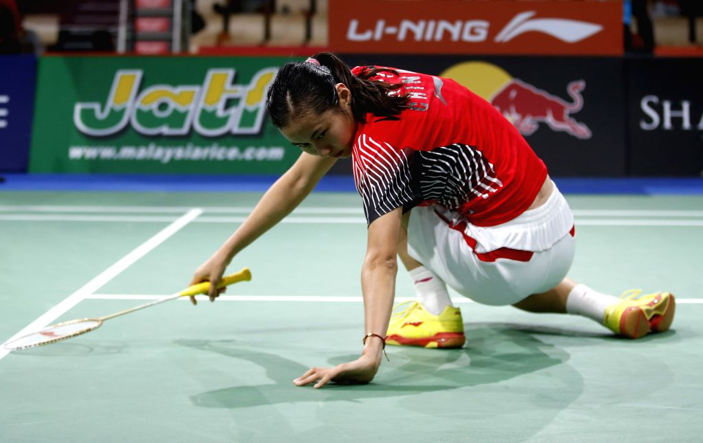 Wang Yihan of China falls down during the Women's Singles Round 3 match against Carolina Marin of Spain on Day 4 of Li Ning BWF World Championships 2014 at ...
