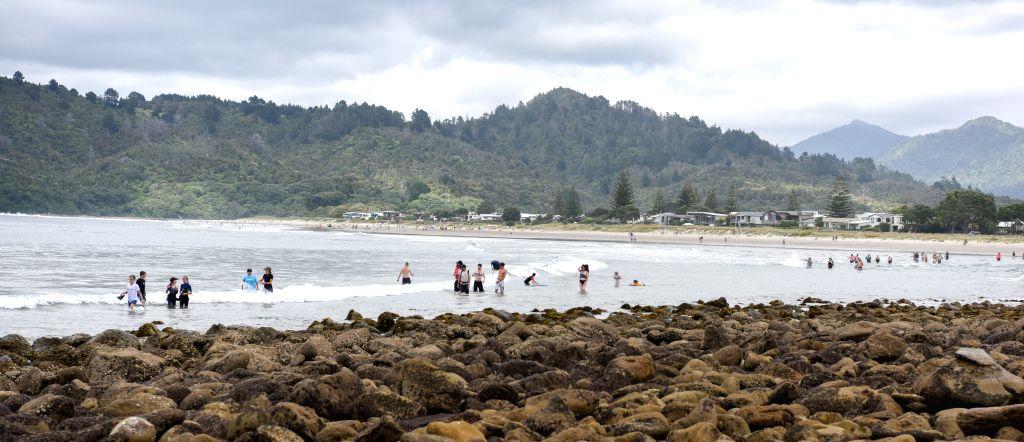 COROMANDEL, Jan. 3, 2019 - Tourists wade through the waves via the low tide path between Whangamata beach and Hauturu Island in Coromandel Peninsula of New Zealand, Jan. 3, 2019.