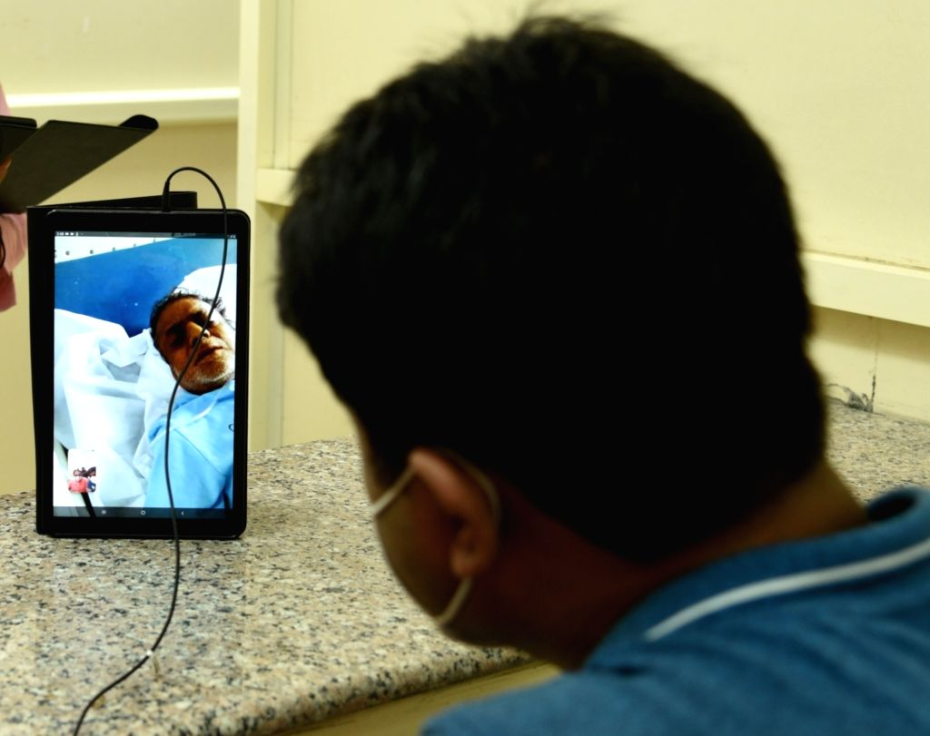 Coronavirus patients admitted at the LNJP Hospital to talk to their relatives through the recently launched video calling facility using tablets installed in every ward of the hospital, in ...