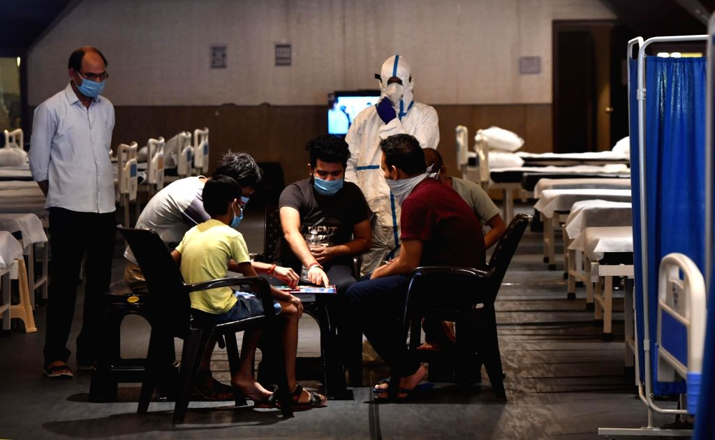 Coronavirus patients play ludo at a banquet hall turned Covd Care Center, in New Delhi on July 5, 2020.