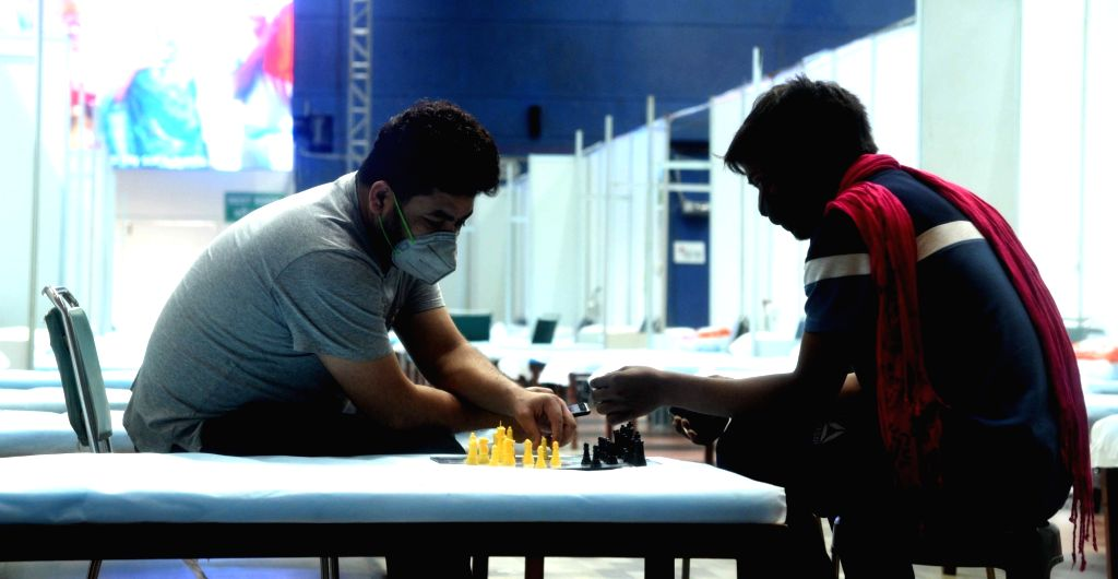 Coronavirus positive patients play Chess at the CWG Village Covid Care Center, in New Delhi on July 13, 2020.