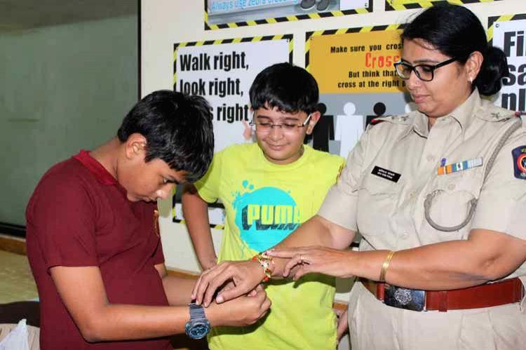 CounZil Kid tying rakhi to a policewomam