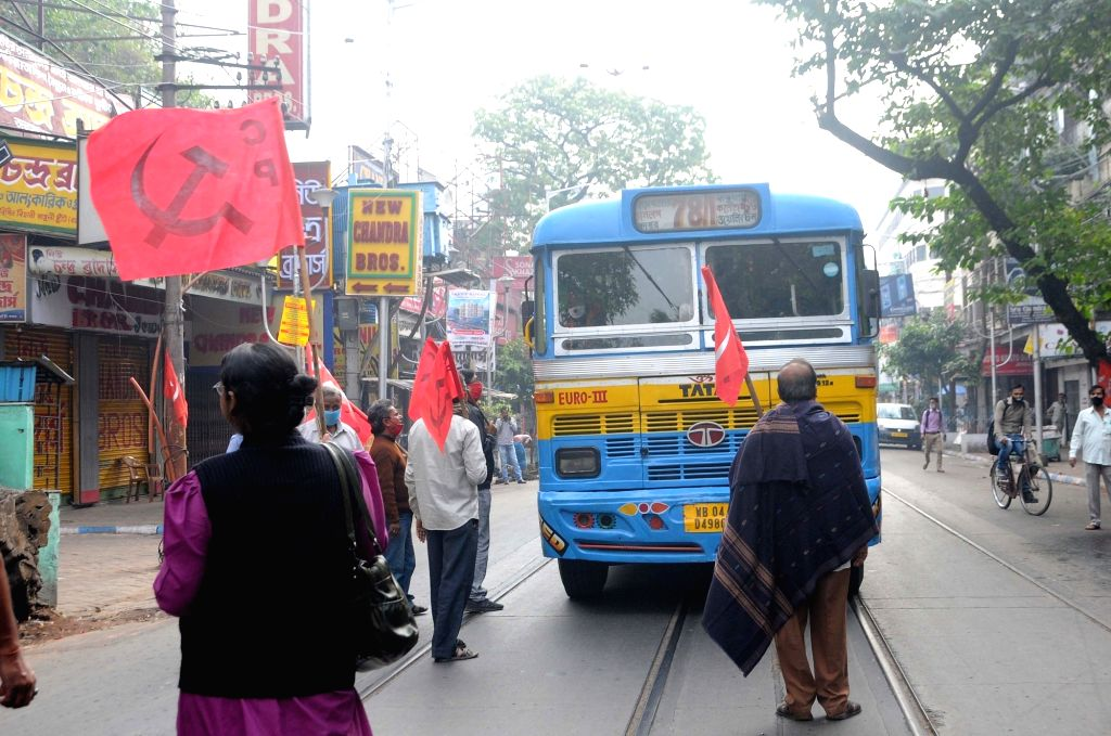 CPI activists block vehicular movement during protest as part of the 24-hour nationwide trade union strike called by the central trade unions against the central government's new farm and ...