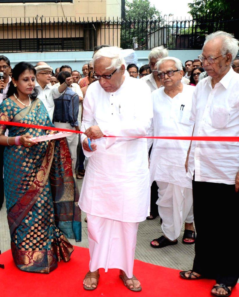 CPI-M leaders Buddhadeb Bhattacharjee, Biman Bose, Surjya Kanta Mishra and others during inauguration of an exhibition on 128th birth anniversary of CPI-M leader Muzaffar Ahmad in Kolkata, ... - Biman Bose and Surjya Kanta Mishra