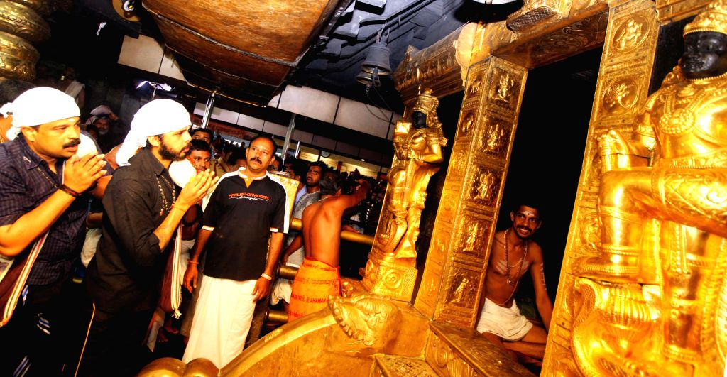 Cricketer S Sreesanth ( 2nd left) and his brother Deepu Shanth prays at Sabarimala Ayyapa temple in Kerala on June 15, 2013. (Photo: IANS)