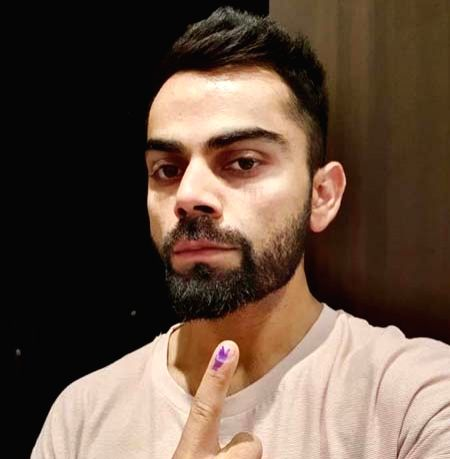 Cricketer Virat Kohli shows his forefinger marked with indelible ink after casting vote during the sixth phase of 2019 Lok Sabha elections, in Gurugram on May 12, 2019. - Virat Kohli
