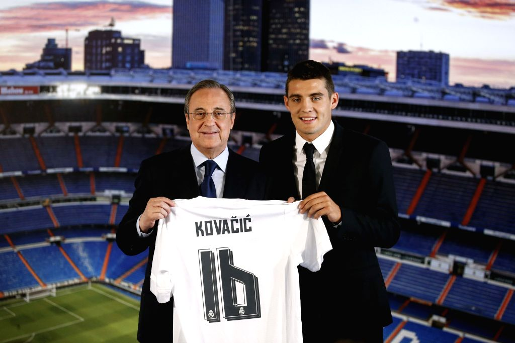 Croatian midfielder Mateo Kovacic (R) poses next to Real Madrid's president Florentino Perez, during his presentation as new player of the team at Santiago Bernabeu in Madrid, Spain, 19 ...