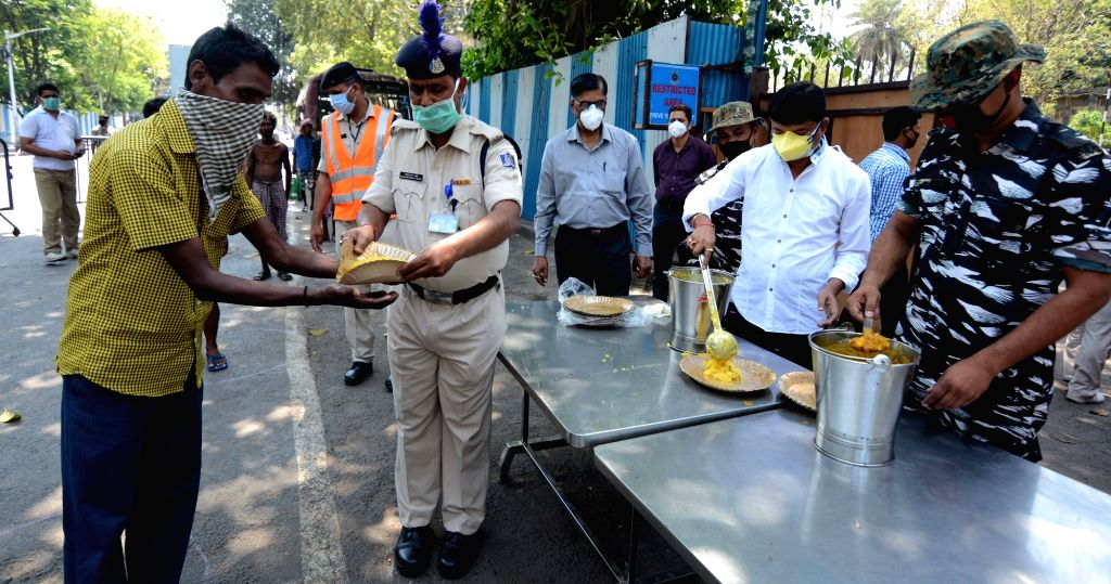 CRPF personnel distribute cooked food among the poor and needy people on Day 5 of the 21-day countrywide lockdown imposed to contain the spread of novel coronavirus, in Kolkata on March 29, ...