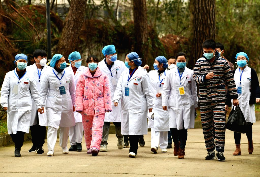 Cured patients accompanied by medical staff walk out of the Jiangjunshan section of the public health center for treatment in Guiyang, southwest China's Guizhou ...