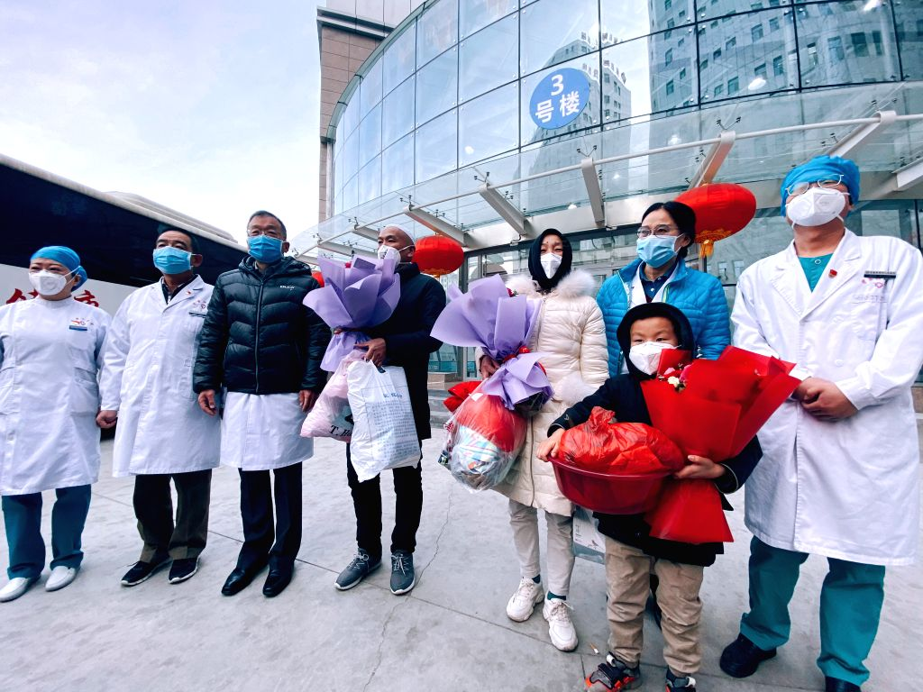 Cured patients pose for a group photo with medical staff at the No.4 People's Hospital in Xining, northwest China's Qinghai Province, Feb. 5, 2020. Three pneumonia ...