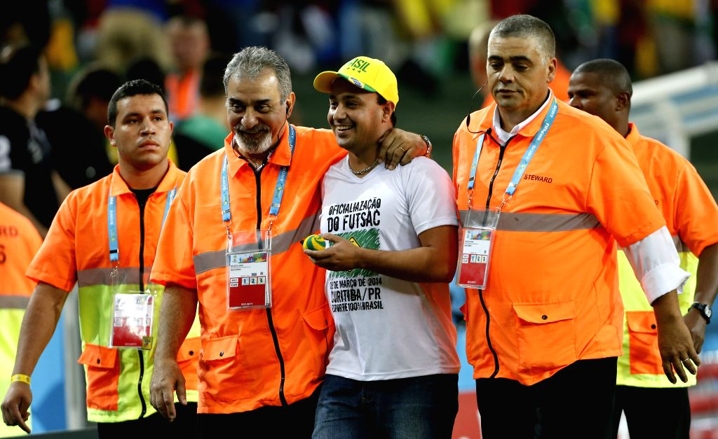 A fan (2nd R) is taken away from the field by securities after a Group F match between Iran and Nigeria of 2014 FIFA World Cup at the Arena da Baixada Stadium in ..
