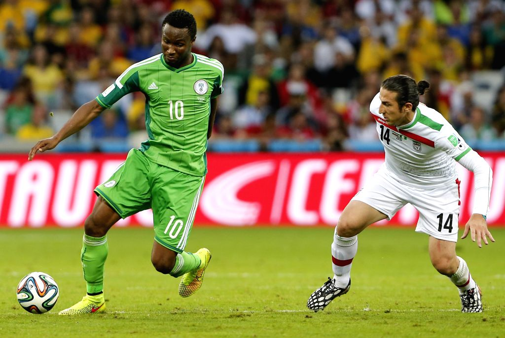 Nigeria's Mikel Obi (L) vies with Iran's Andranik Timotian during a Group F match between Iran and Nigeria of 2014 FIFA World Cup at the Arena da Baixada Stadium ..