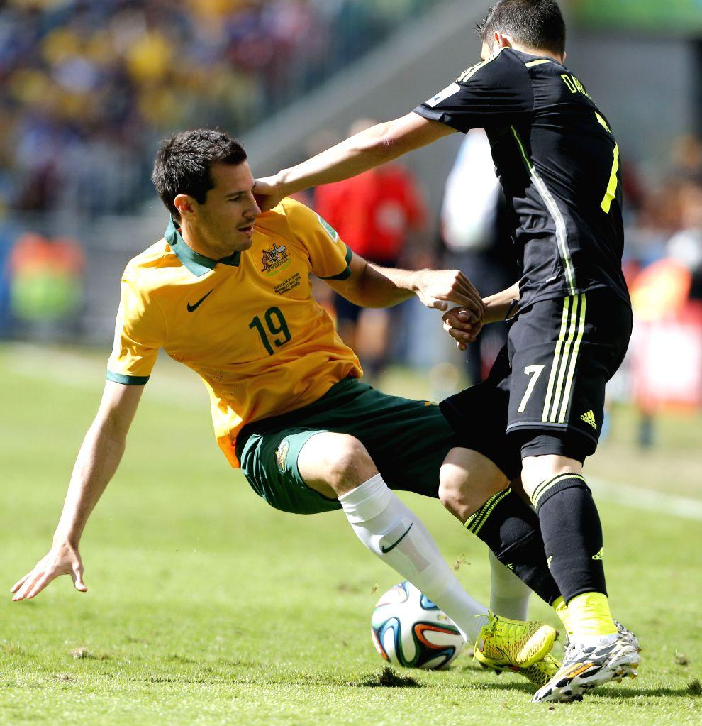 Australia's Ryan McGowan (L) vies with Spain's David Villa during a Group B match between Australia and Spain of 2014 FIFA World Cup at the Arena da Baixada ...