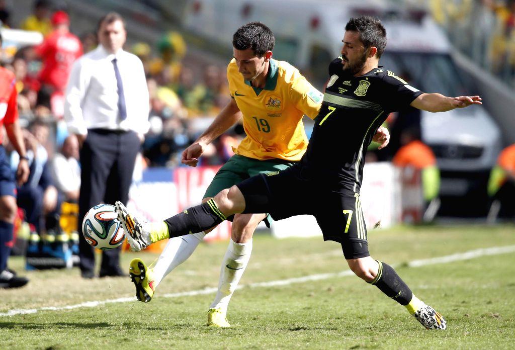Spain's David Villa (R) vies with Australia's Ryan McGowan during a Group B match between Australia and Spain of 2014 FIFA World Cup at the Arena da Baixada Stadium ..