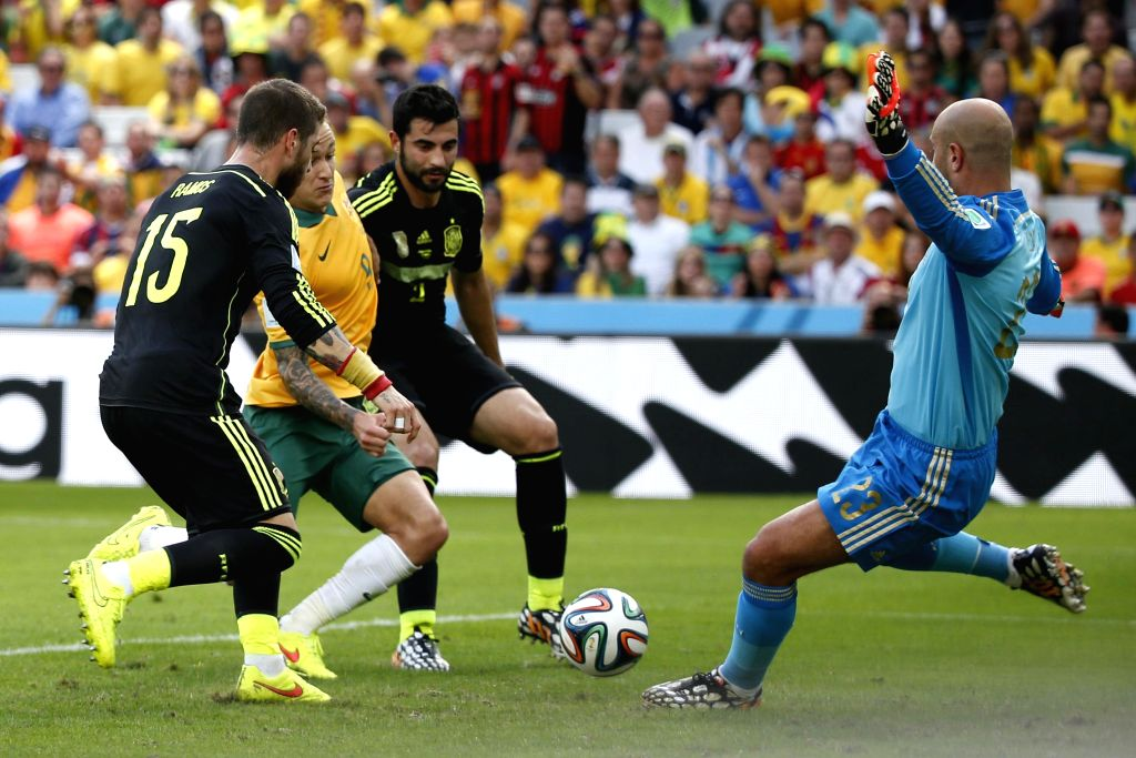 Spain's goalkeeper Pepe Reina (R) blocks the ball during a Group B match between Australia and Spain of 2014 FIFA World Cup at the Arena da Baixada Stadium in ...
