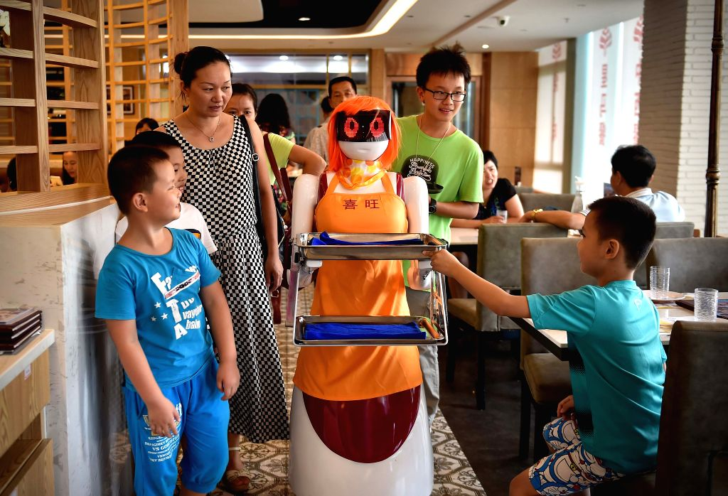 Customers look at the robot waiter in Haikou, capital of south China's Hainan Province, Aug. 3, 2015. A robot waiter was introduced to a restaurant in Haikou. ...
