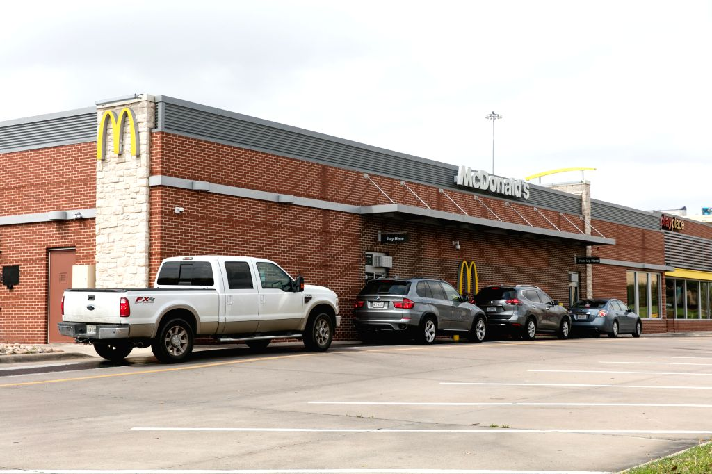 Customers wait in their cars at McDonald's drive-thru service in Frisco, on the outskirts of Dallas, Texas, the United States on March 19, 2020. U.S. state of ...
