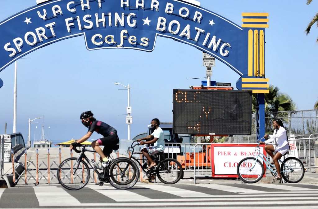 Cyclists pass the closed entrance to Santa Monica beach in Los Angeles County, the United States, on July 4, 2020. Nearly all Los Angeles County beaches have ...