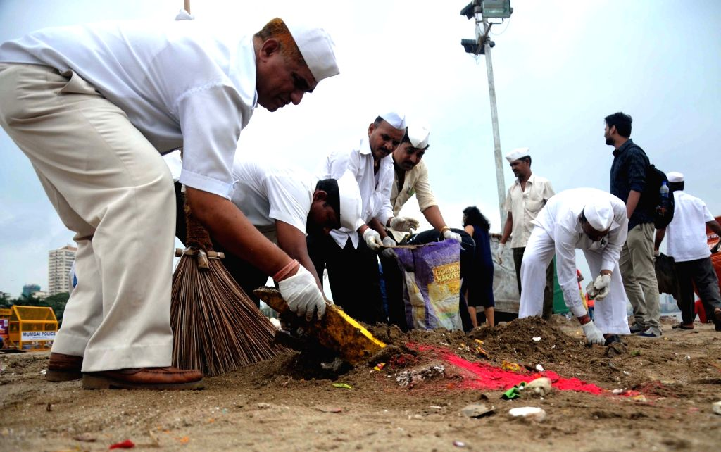 Dabbawalas, who carry the lunch boxes clean up  sea beach a day after Ganesh idol immersions at Girgam, Mumbai on Sept 16, 2016.