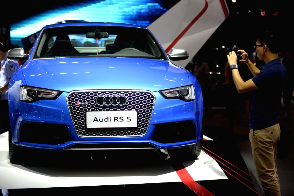 A visitor takes photos of an Audi RS 5 car at the 19th Dalian International Automotive Exhibition in Dalian, northeast China's Liaoning Province, Aug. 27, 2014. The .