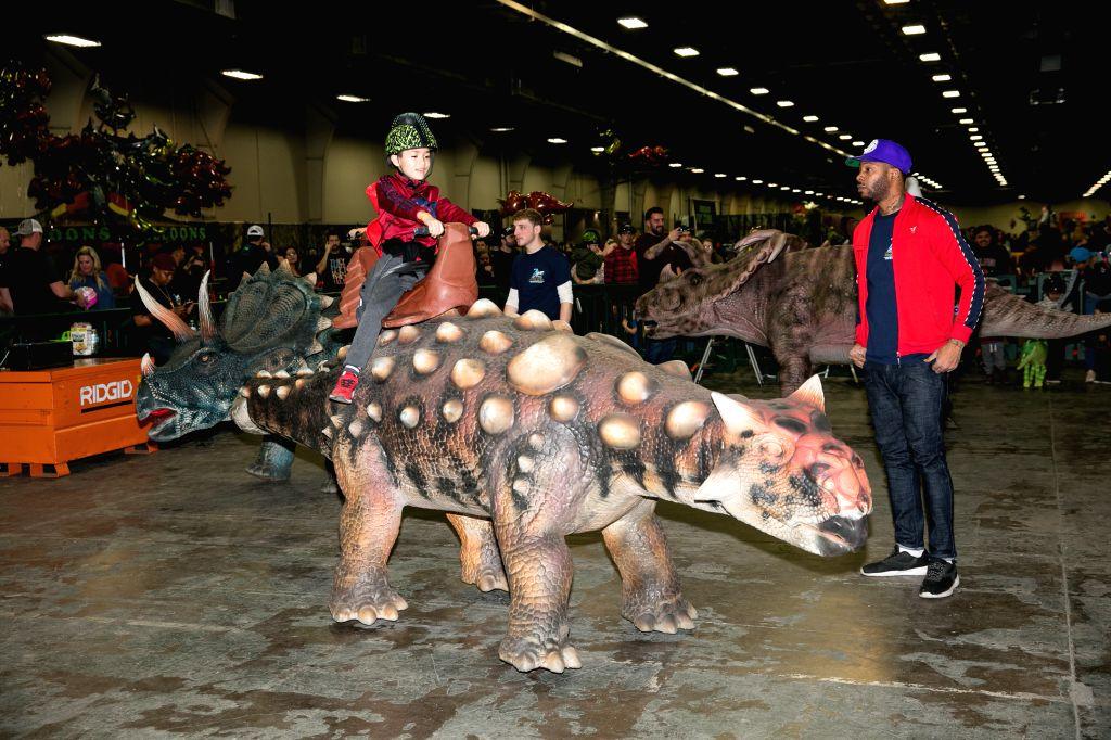 DALLAS, Dec. 8, 2019 - A child rides a dinosaur model at the Jurassic Quest exhibition in Dallas, Texas, the United States, on Dec. 8, 2019. Dinosaur exhibition Jurassic Quest is held in Dallas on ...