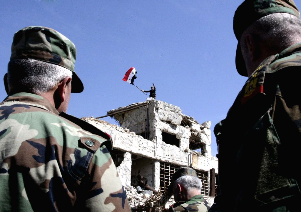 DAMASCUS, April 1, 2018 - A soldier waves Syrian national flag on a government building in the recently recaptured Jobar neighborhood in the Eastern Ghouta countryside of Damascus, Syria, on April 1, ...