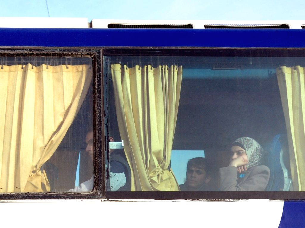 DAMASCUS, April 2, 2018 - Family members of Islam Army are seen on a bus departing the district of Douma in Eastern Ghouta through a crossing point in Wafideen area, northeast of Damascus, Syria, on ...