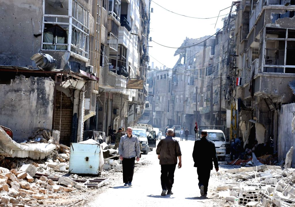 DAMASCUS, April 3, 2018 - People walk in a street in the town of Arbeen in the Eastern Ghouta countryside of Damascus, Syria, on April 2, 2018. The last batch of rebels left the towns of Jobar, ...