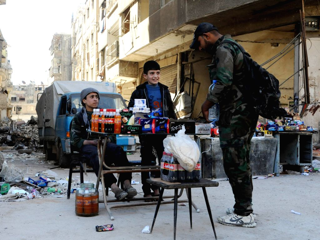 DAMASCUS, April 4, 2018 - Syrian boys sell food to a soldier in the town of Zamalka in Eastern Ghouta countryside of Damascus, Syria, on April 4, 2018. A total of 635 Islam Army militants and their ...