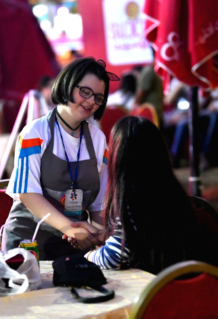 DAMASCUS, Aug. 11, 2019 - A young girl with Down Syndrome serves in a coffee shop during a festival held in Damascus on Aug. 6, 2019. Young Syrians with Down Syndrome are taking part in a month-long ...