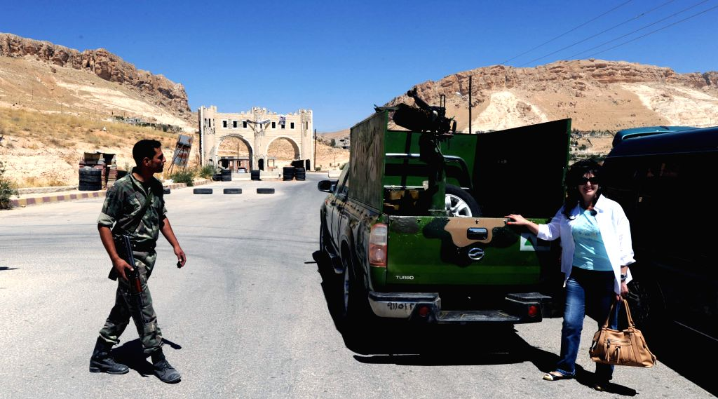 A woman poses with a pick-up loaded with weapons in the historic Christian town of Maaloula, north of Damascus, capital of Syria, Aug. 21, 2014. Maaloula is one of