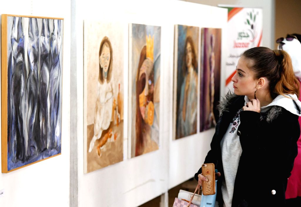 "DAMASCUS, Dec. 4, 2019 - A visitor views paintings in a gallery in Damascus, Syria, on Dec. 4, 2019. The art exhibition was held on the occasion of an international campaign dubbed ""16 Days of ..."