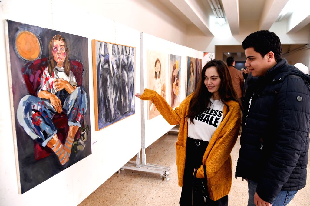 "DAMASCUS, Dec. 4, 2019 - Visitors view paintings in a gallery in Damascus, Syria, on Dec. 4, 2019. The art exhibition was held on the occasion of an international campaign dubbed ""16 Days of ..."