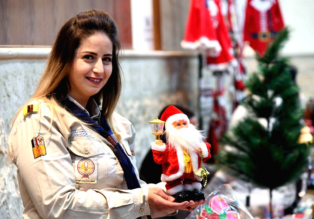 DAMASCUS, Dec. 5, 2019 - A woman shows a mini Santa Claus toy during a Christmas bazaar in Damascus, Syria, on Dec. 5, 2019. Around 40 women showcased their handmade Christmas decorations in the ...