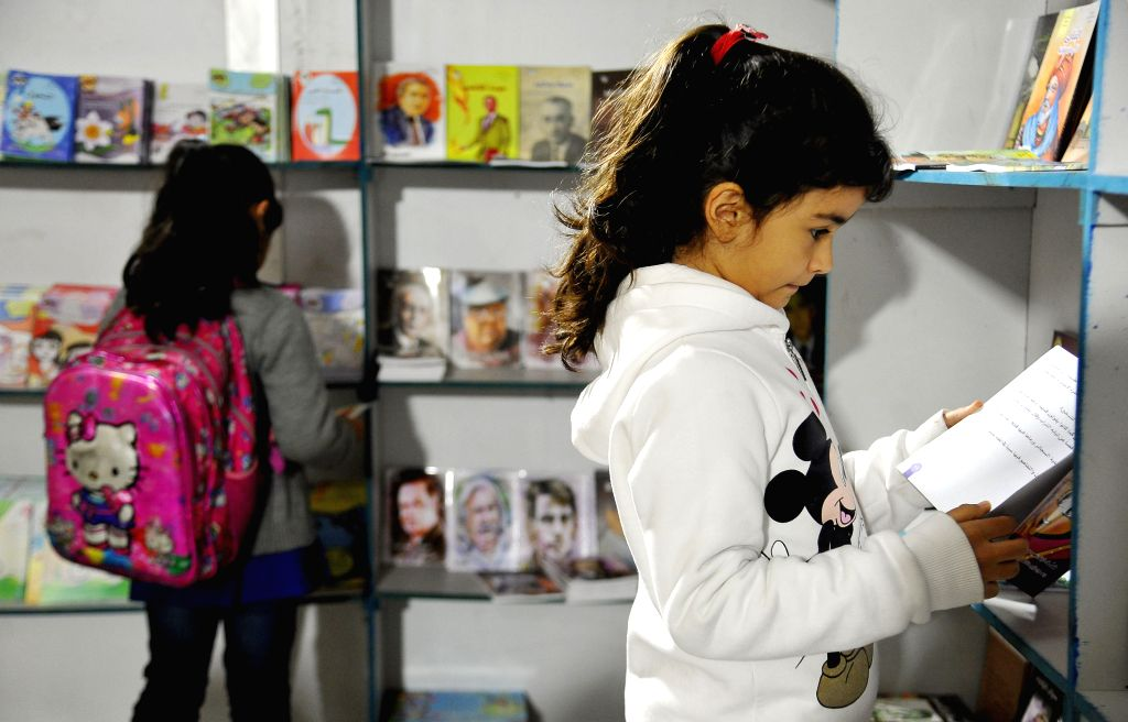 DAMASCUS, Dec. 5, 2019 - Girls read books during a book fair for children in Damascus, Syria, on Dec. 5, 2019. The Syrian Ministry of Culture held a book fair for children on Thursday.