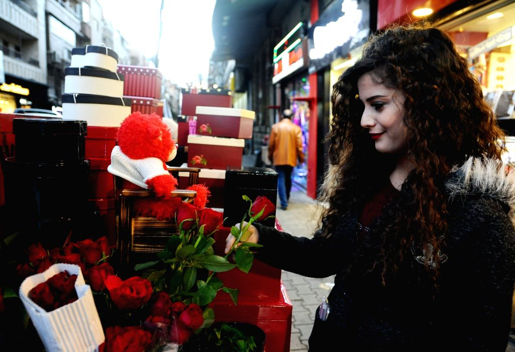DAMASCUS, Feb. 13, 2018 - A woman picks a rose outside a shop a day ahead of the Valentine's Day in Damascus, capital of Syria, on Feb. 13, 2018.