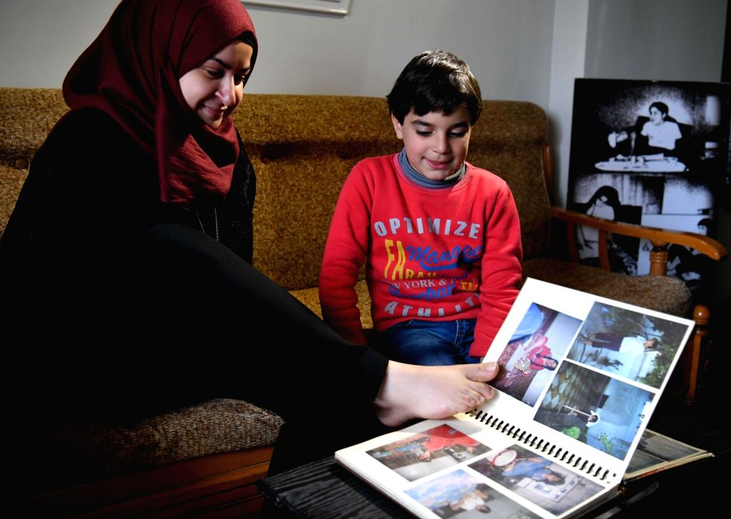 DAMASCUS, Feb. 21, 2019 - Dua al-Bustati, 28, shows her nephew old photos in her house in the suburb of Sehnaya in the countryside of Damascus, capital of Syria, Feb. 20, 2019. Dua al-Bustati was ...