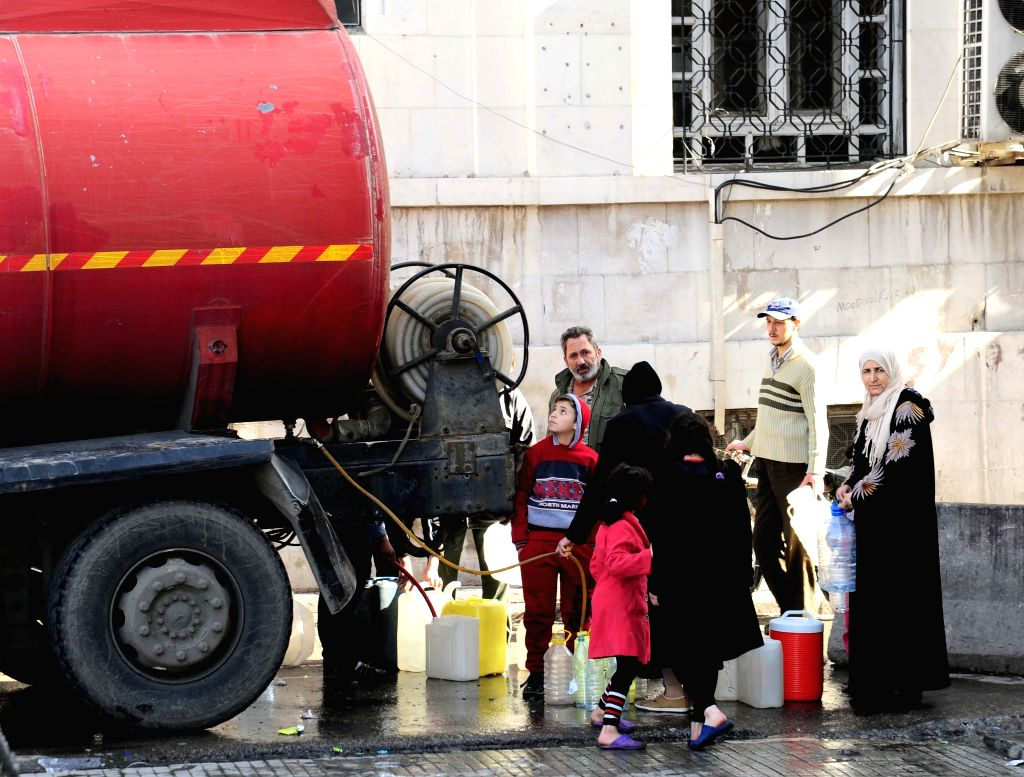 DAMASCUS, Jan. 12, 2017 - Syrians fill up their jerrycans with water from a street water tanker in Damascus, capital of Syria, on Jan. 12, 2017. Damascenes have been struggling to secure their needs ...