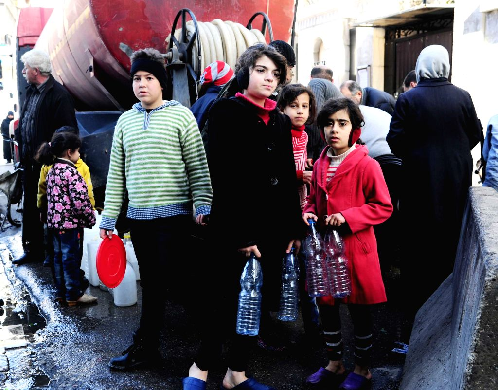 DAMASCUS, Jan. 12, 2017 - Syrians wait to fill up their plastic bottles with water from a street water tanker in Damascus, capital of Syria, on Jan. 12, 2017. Damascenes have been struggling to ...