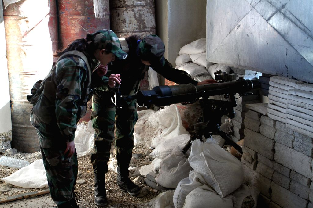 Syrian fighters, members of the Girls Commando Battalion, aim a weapon at the demarcation lines in the Eastern Ghouta in the countryside of Damascus, Syria, March ...