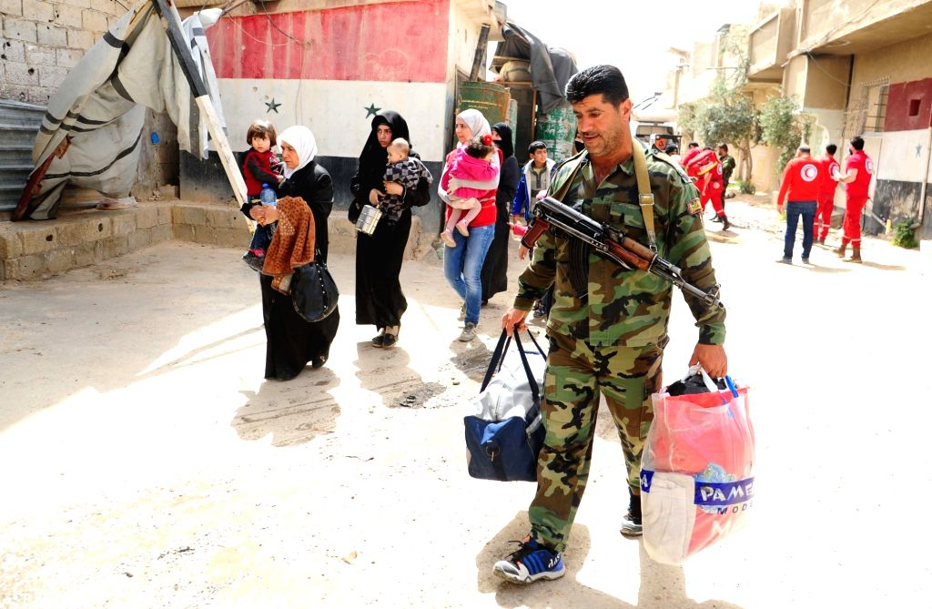 DAMASCUS, March 27, 2018 - A Syrian soldier helps civilians carrying their belongings as they reach government-controlled Wafidin area, northeast of Damascus, Syria, on March 27, 2018. Hundreds of ...