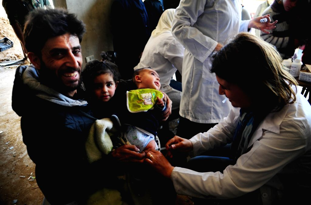 DAMASCUS, March 29, 2018 - A doctor administers a vaccine to a child in the recently-captured Harasta city in the Eastern Ghouta, Damascus, capital of Syria, on March 29, 2018. The city of Harasta, ...