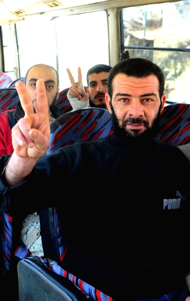 DAMASCUS, March 31, 2018 - Freed Syrian soldiers flash victory signs upon arriving at a government-controlled area in the capital Damascus' Eastern Ghouta countryside on March 31, 2018. Eight Syrian ...