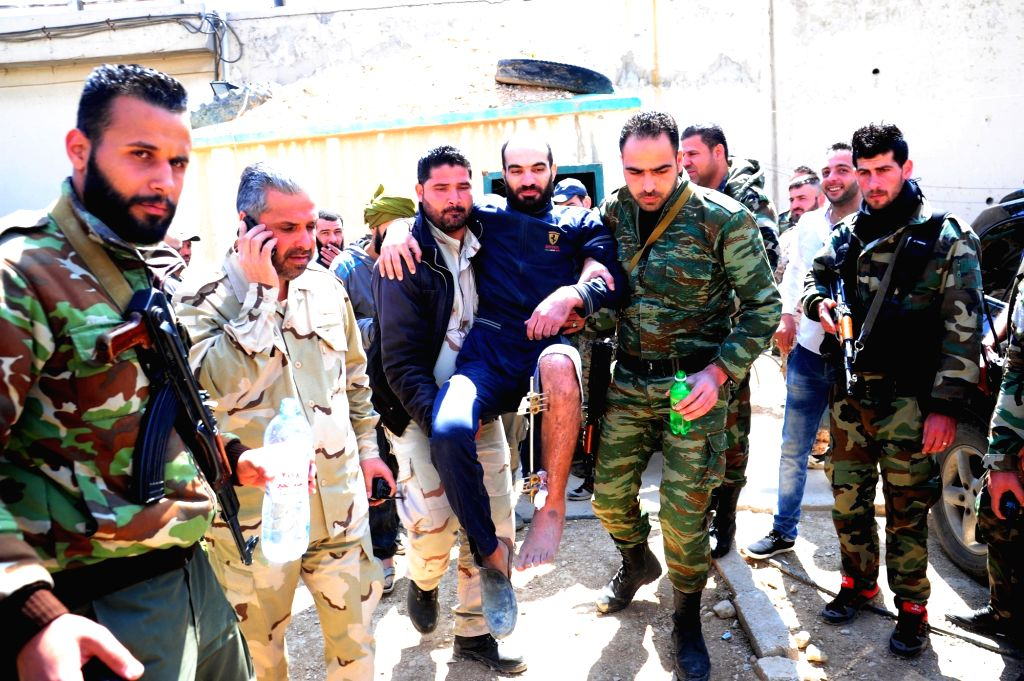 DAMASCUS, March 31, 2018 - Syrian soldiers carry a wounded freed soldier (C) in the capital Damascus' Eastern Ghouta countryside on March 31, 2018. Eight Syrian soldiers were set free from rebels' ...