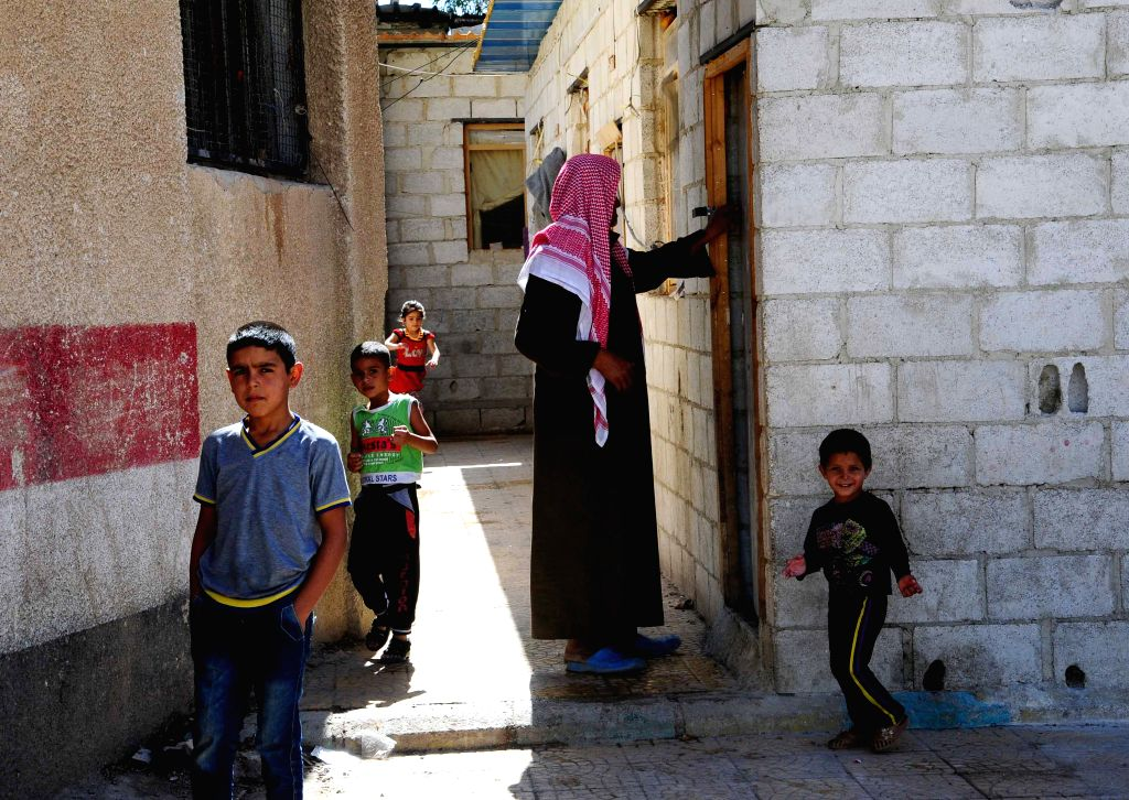 DAMASCUS, Oct. 15, 2016 - A displaced Syrian family stand outside their housing unit in a displacement center in the town of Hirjalleh, countryside of Damascus, capital of Syria, on Oct.15, 2016. The ...