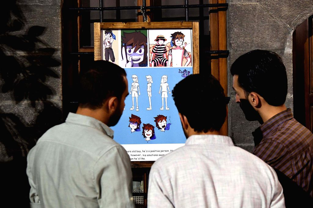 DAMASCUS, Oct. 9, 2019 - People view a piece of cartoon work during a fair in the old city of Damascus, Syria, on Oct. 9, 2019. The fair highlighted the works of cartoon artists in Syria.