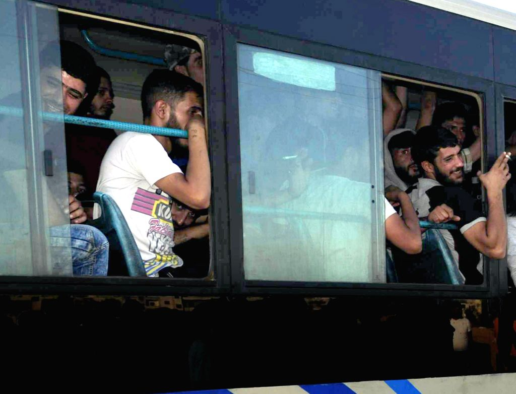 DAMASCUS, Sept. 11, 2016 - Syrian rebels wait for evacuation by the government after surrendering themselves in the rebel-held Muadamiyeh, rural Damascus, capital of Syria, Sept. 10, 2016. Several ...
