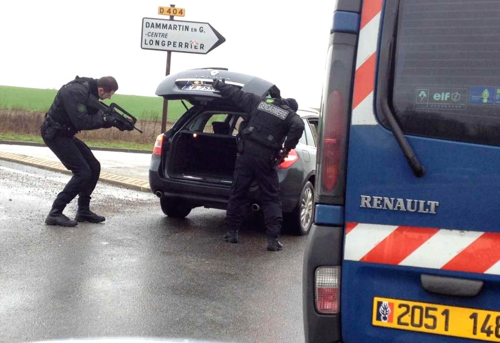 DAMMARTIN-EN-Policemen check a car in Dammartin-en-Goele, northeast of Paris, where two brothers suspected of Charlie Hebdo attack held one person hostage as police ..