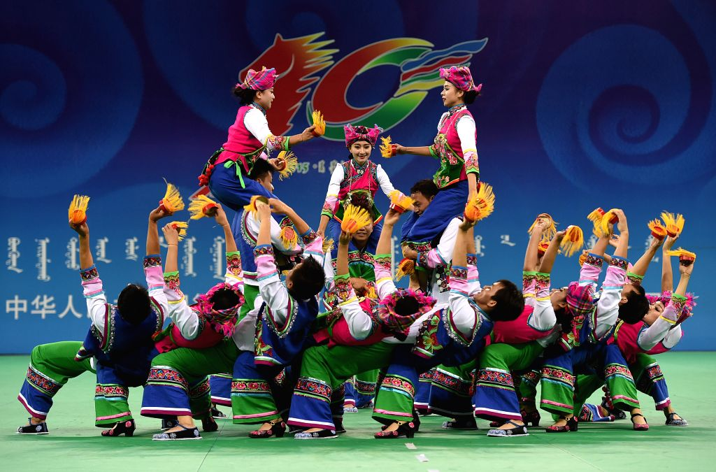 Dancers from southwest China's Yunnan Province perform during the 10th National Traditional Games of Ethnic Minorities of China in Ordos, north China's Inner Mongolia ...