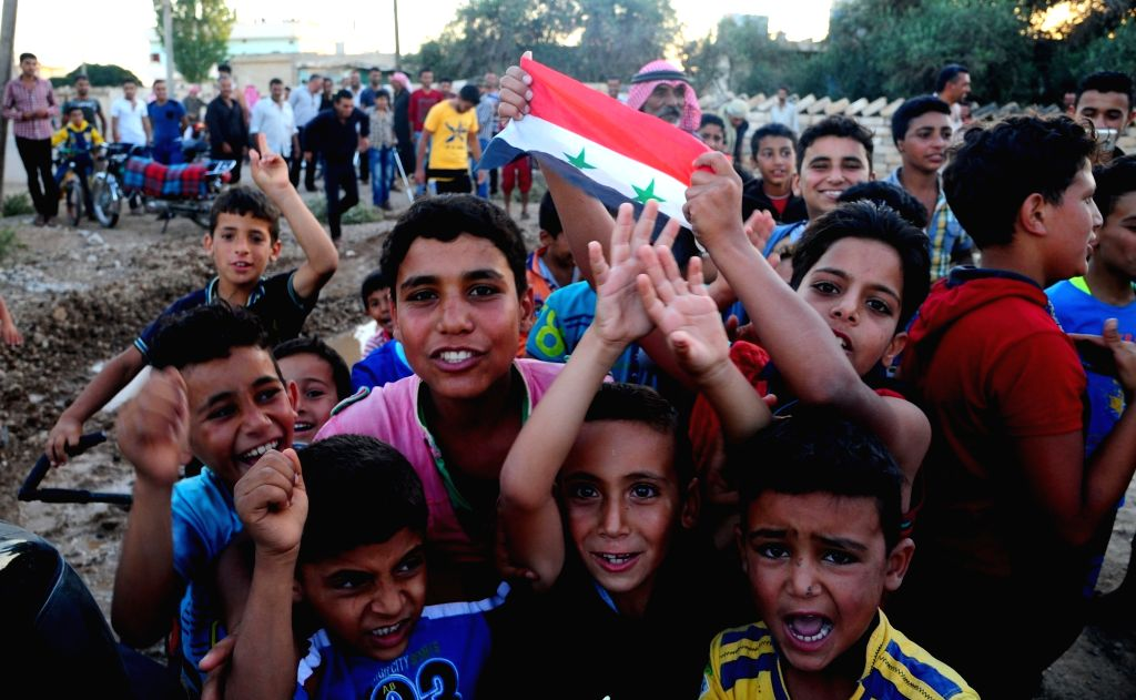 DARAA, July 9, 2018 - Boys hold a Syrian national flag as they welcome Syrian army in the Kharab al-Shahem town in the western countryside of Daraa province in southern Syria on July 8, 2018. The ...